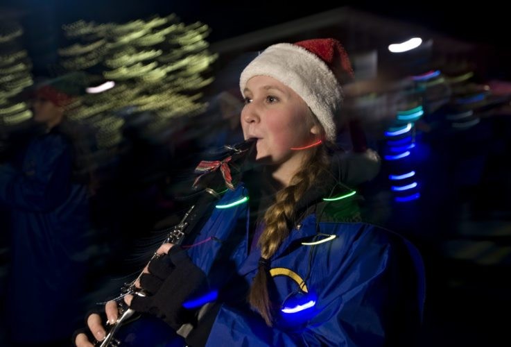 Lilly Frank, 16, of Woodstock plays the clarinet as the Central Falcons Marching Band parades outside the old courthouse during the town's Light Up Woodstock held on Friday night. The event featured carols by the Peter Muhlenberg chorus, the lighting of the town's Christmas tree and the dedication of the Rotary Club's town clock.  Rich Cooley/Daily